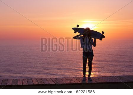 Beautiful girl holding a skateboard with the sunset in the background