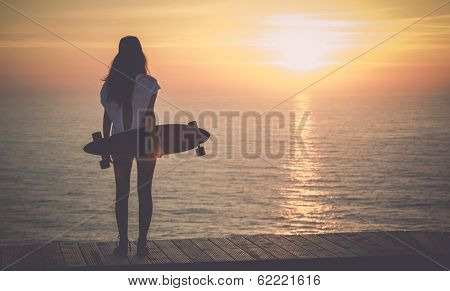 Beautiful girl with a skateboard looking to the sunset