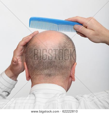 Funny picture of a hairless man with comb.