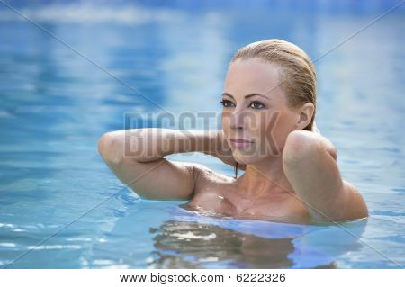 Beautiful Blond Woman In A Blue Swimming Pool