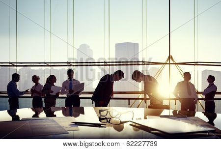 Group of business people and men bowing reflected onto table with documents.