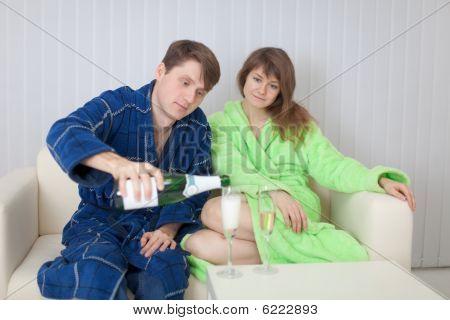 Homem derrama a mulher no vidro de um vinho espumante