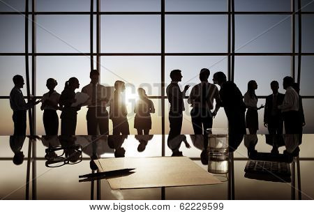 Group of Business People Discussing at Sunset Reflected Onto Table with Documents