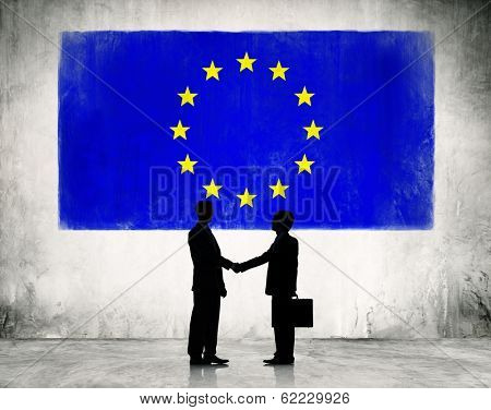 Businessmen Shaking Hands at European Union Flag