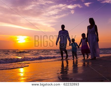 Family Walking on The Beach at Sunset