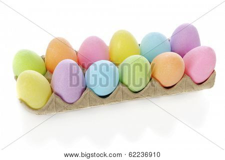 A dozen pastel colored Easter eggs in a carton.  On a white background.