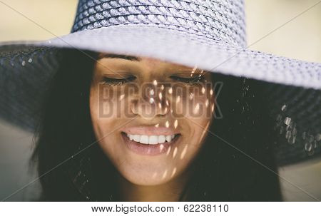 Happy smiling girl wearing a blue hat on the sea beach