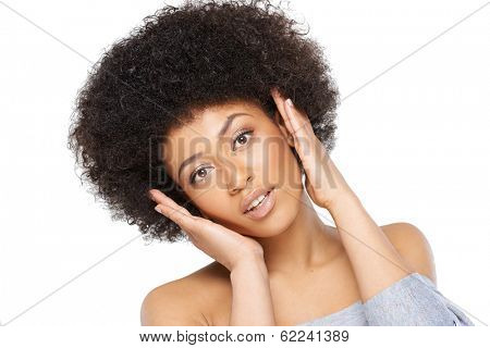 Happy surprised young African American woman in a sexy off the shoulder top looking at the camera with an excited look and her hands raised to her head