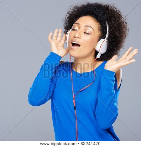Happy beautiful young African American woman singing along to the music on her headphones as she enjoys the tunes, on grey
