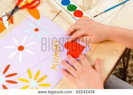 Child Glues Paper Heart
