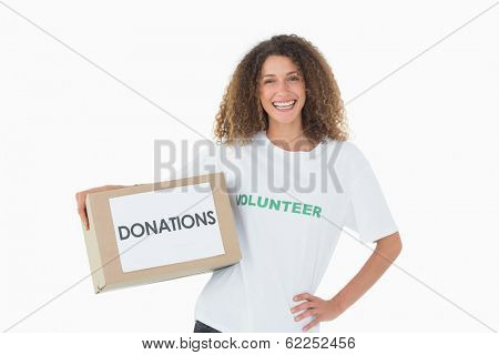 Smiling volunteer holding a box of donations with hand on hip on white background