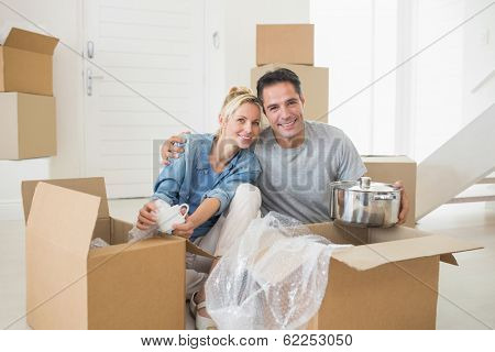 Portrait of a smiling couple unpacking boxes in a new house