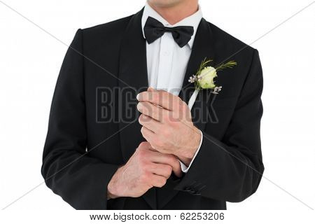 Mid section of groom adjusting cuff links before wedding over white background