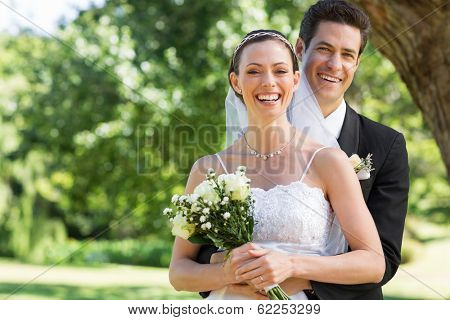 Portrait of newly wed couple with flower bouquet in park