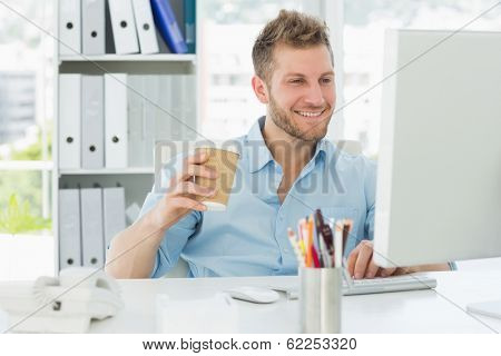 Smiling man working at his desk drinking a take away coffee in creative office