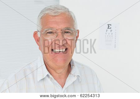 Portrait of a smiling senior man with eye chart in the background at medical office