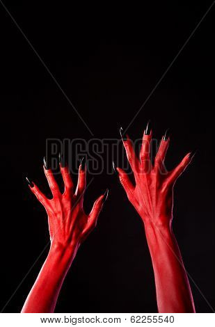 Red devil hands with black nails, Halloween theme, studio shot on black background