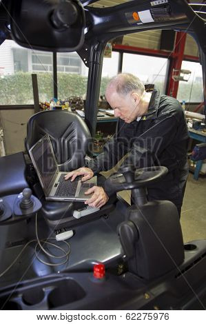 Mechanic checking the statistics of a forklift on a laptop, using its mechatronical interface. Mechatronic technology in internal transport
