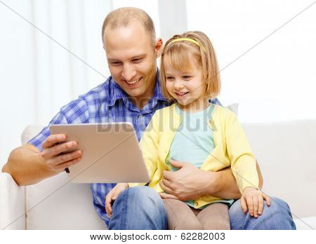 family, children, parenthood, technology and internet concept - happy father and daughter with tablet pc computer at home