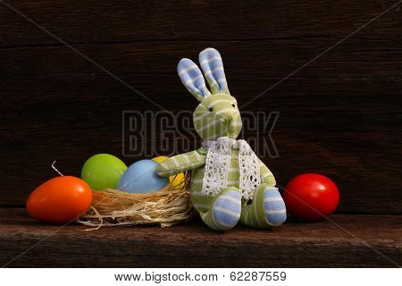 Easter Bunny Toy Raffia Nest Eggs On Rough Background