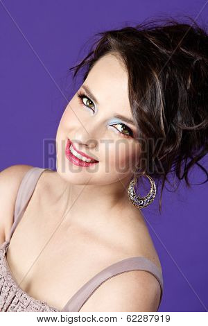 Attractive young woman in beige lace dress and messy brown hair on purple studio background