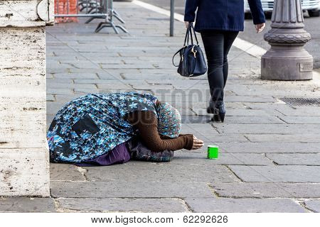 a beggar begging on a street in the