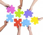 stock photo of debate  - Human hands holding jigsaw puzzle - JPG
