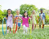 stock photo of hula hoop  - Diverse Children Playing With Hula Hoops in the Park - JPG