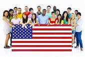 stock photo of united we stand  - Large Group of People Holding American Flag Board - JPG