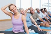 image of senior class  - Female trainer with class stretching neck in row at yoga class - JPG