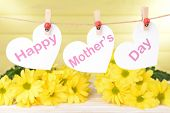 stock photo of mummy  - Happy Mothers Day message written on paper hearts with flowers on yellow background - JPG