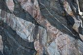 pic of gneiss  - This image shows a band of blueish grey banded Lewisian Gneiss from left to right about the middle and lower section of the image - JPG
