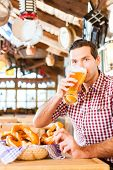 Bavarian man wearing traditional dress drinking beer in German restaurant