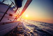 stock photo of sails  - Sail boat with set up sails gliding in open sea at sunset - JPG