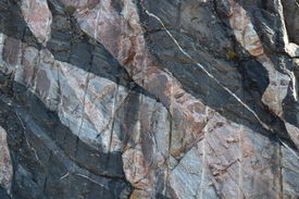 picture of gneiss  - This image shows a band of blueish grey banded Lewisian Gneiss from left to right about the middle and lower section of the image - JPG
