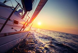 foto of sailing vessels  - Sail boat with set up sails gliding in open sea at sunset - JPG