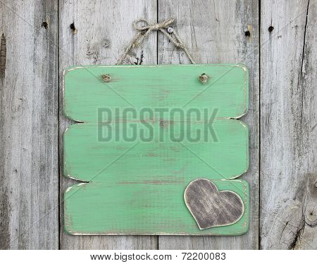 Blank green sign with wooden heart hanging on old weathered wood door