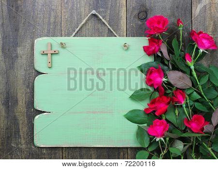 Rustic green blank sign with wooden cross and flower border of red roses hanging on wood door