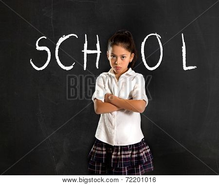 Hispanic Moody Little Girl In Uniform Standing Upset In Front Of Blackboard
