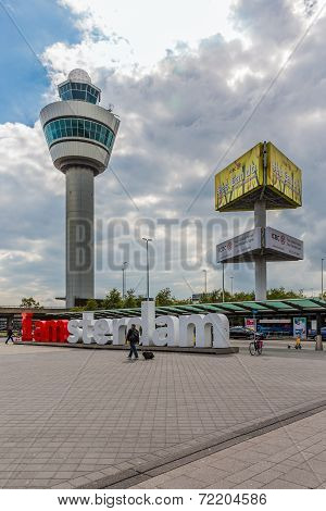 Airport Square With Control Tower, Advertising Pillar And Passing Travellers