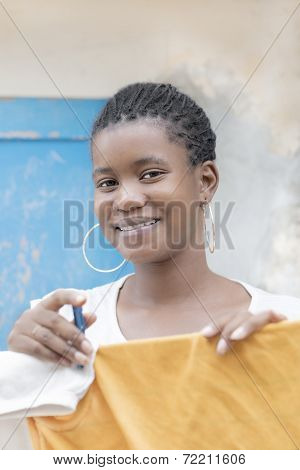 Young Afro beauty drying her clothes on the line