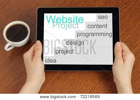 Hand hold tablet pc with website project's development steps