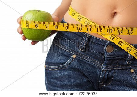 Woman measuring her waist and holding fresh green apple in hand