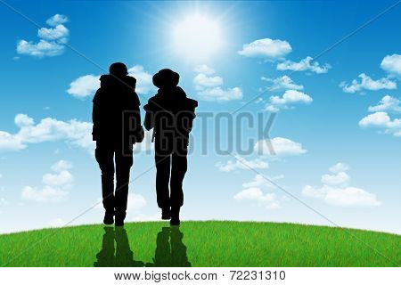 Couple Of Backpackers Walking On A Top Of A Hill Towards The Sun