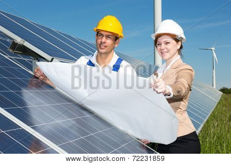Photovoltaic Engineers With Construction Plan At Solar Panels