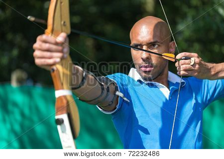 archer at shooting range with bow and arrow