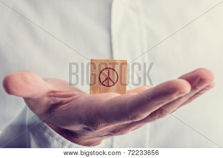 Man Holding A Wooden Block With The Peace Sign