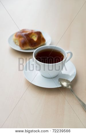 White Cup Of Tea And Sweet Patty On The Table