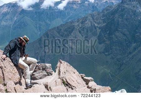 Man Posts Message To Social Networks, Sitting On The Edge Of The Cliff Colca Valley In Peru
