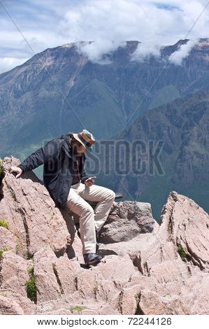 Tourist Sends Status In Social Networks, Sitting Over The Precipice Of Colca Canyon, Arequipa, Peru